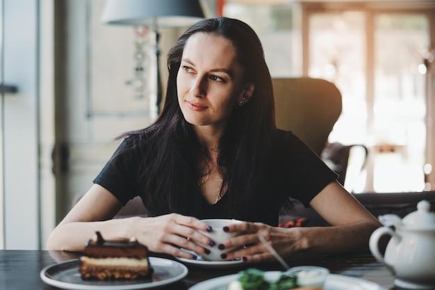 Mujer sentada en la cafetería con una taza de café y sonriendo