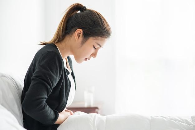 Una mujer sentada en la cama con dolor abdominal y presionando su mano sobre su estómago.