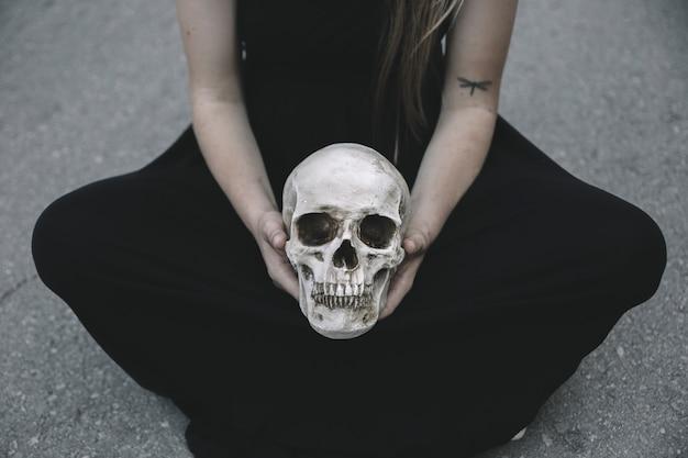 Mujer sentada en la carretera sosteniendo el cráneo decorativo del hombre entre las rodillas
