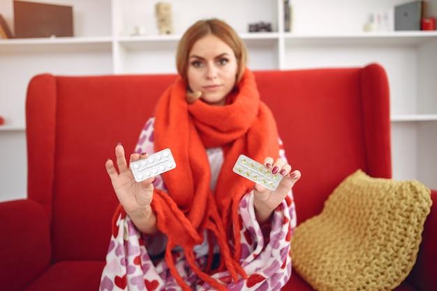 Mujer sentada en casa con un resfriado y tomando pastillas