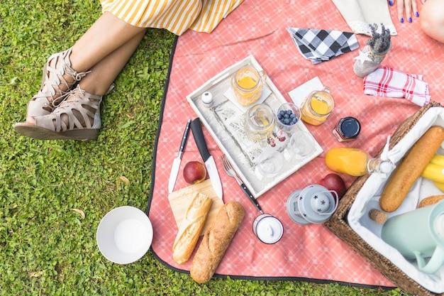 Mujer sentada cerca de la merienda en manta en picnic