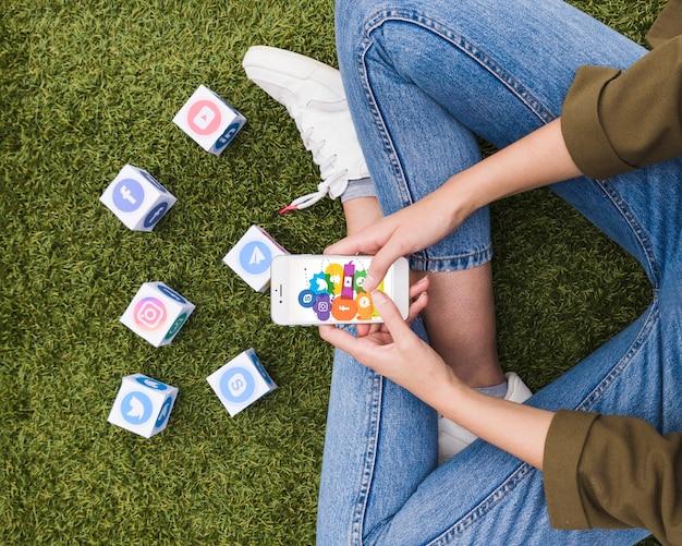 Mujer sentada en el césped con la aplicación de redes sociales en el teléfono móvil