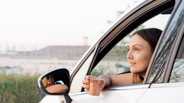Mujer sentada en el coche con el brazo a través de la ventana abierta y un vaso de plástico con una bebida en la mano