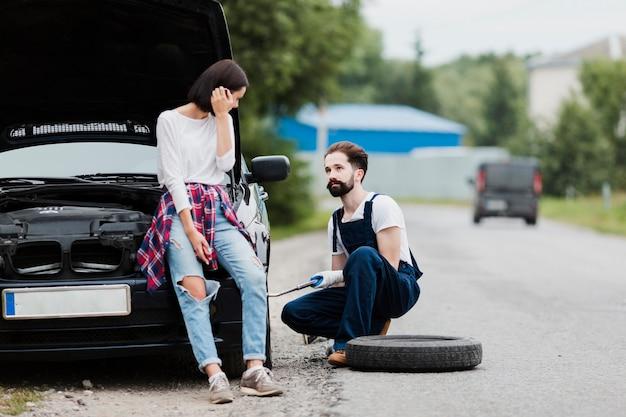 Mujer sentada en el coche y el hombre cambiando neumáticos