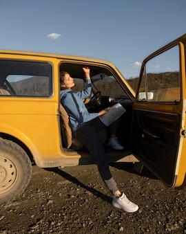 Mujer sentada en el coche con mapa de tiro completo
