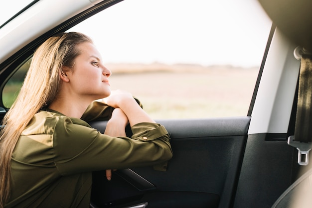 Mujer sentada en el coche y mirando a otro lado