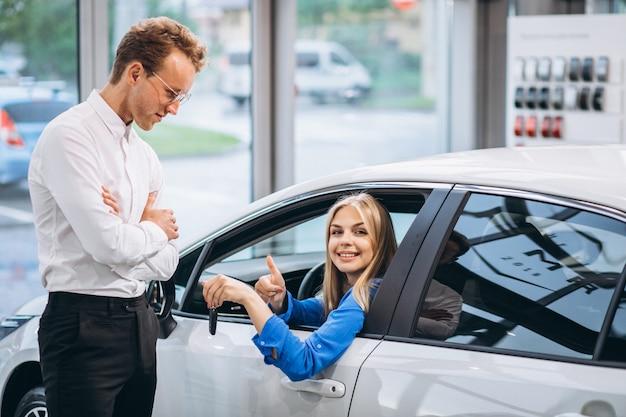 Mujer sentada en el coche y recibir las llaves en una sala de exposición de automóviles