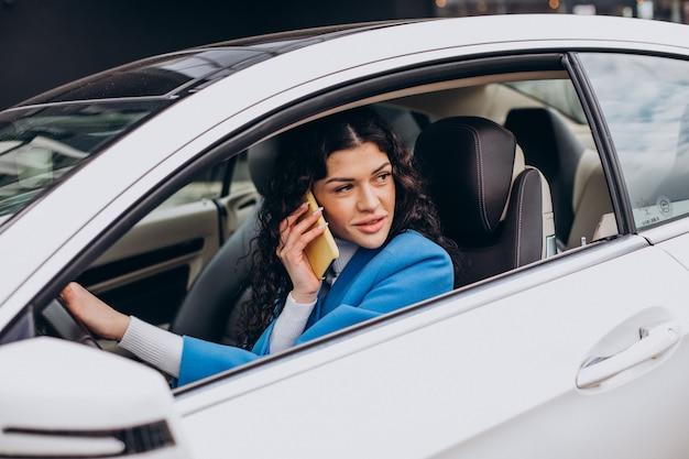 Mujer sentada en el coche y mediante teléfono móvil