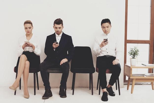 La mujer está sentada con los compañeros de trabajo de los hombres.