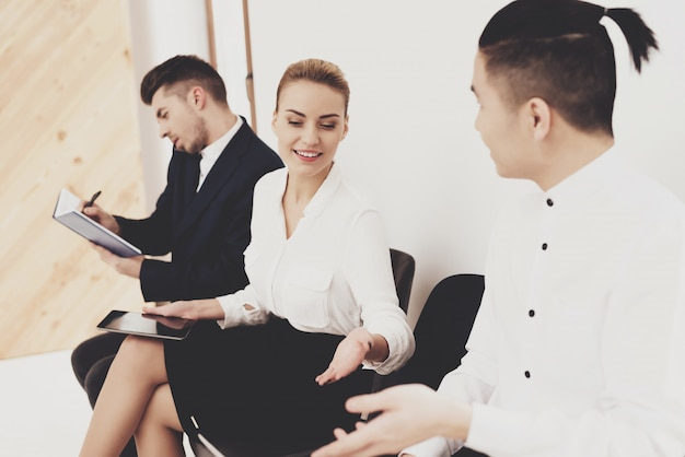 La mujer está sentada con compañeros de trabajo en la oficina
