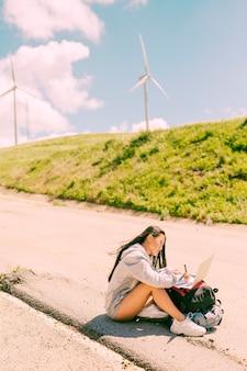 Mujer sentada en el costado del camino y trabajando en la computadora portátil colocada en las mochilas