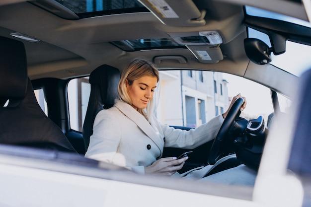 Mujer sentada dentro del auto eléctrico mientras carga