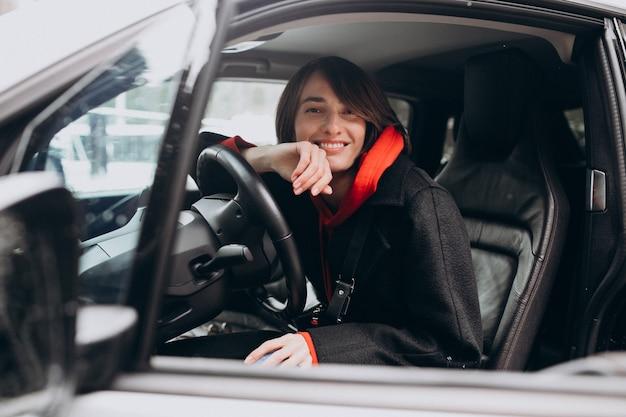 Mujer sentada dentro del auto eléctrico mientras lo carga