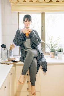Mujer sentada en el worktop de la cocina que bebe el jugo