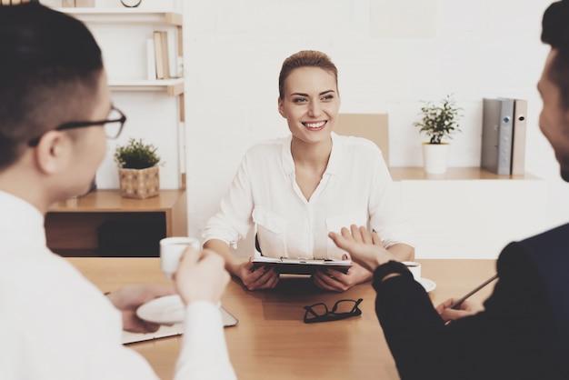 La mujer está sentada en la entrevista de trabajo.