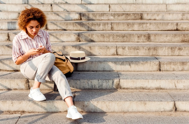 Mujer sentada en las escaleras con espacio de copia