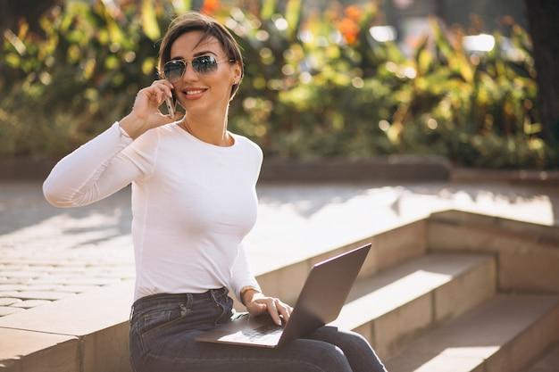 Mujer sentada en las escaleras y trabajando en la computadora portátil