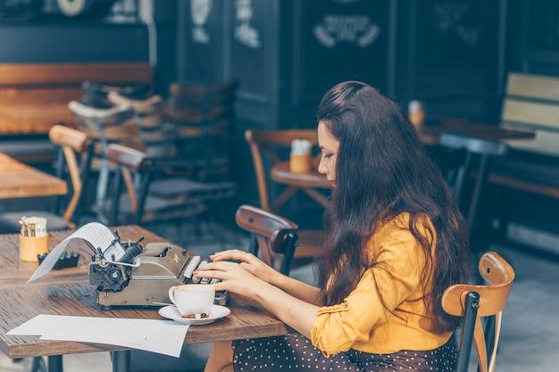 Mujer sentada y escribiendo algo en la máquina de escribir en la terraza del café en la parte superior amarilla y falda larga durante el día y mirando pensativo