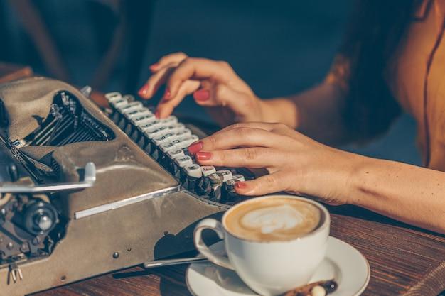 Mujer sentada y escribiendo algo en la máquina de escribir en la terraza del café en la parte superior amarilla y falda larga durante el día