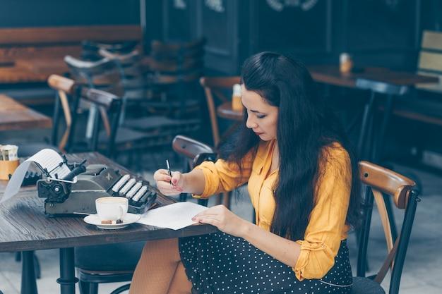 Mujer sentada y escribiendo algo en papel en la terraza del café en la parte superior amarilla y falda larga durante el día y mirando pensativo