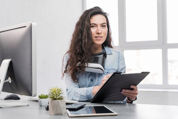 Mujer sentada en un escritorio y escribiendo en el portapapeles