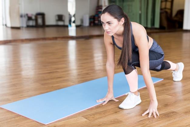 Mujer sentada y estiramiento en gimnasio