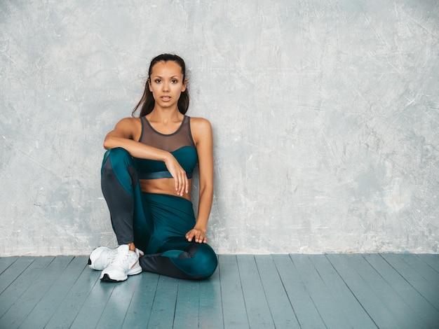 Mujer sentada en el estudio cerca de la pared gris