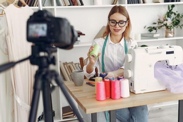 Mujer sentada en estudio y coser tela