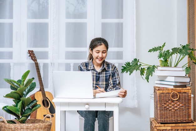 Una mujer sentada felizmente con una computadora portátil en la mesa.