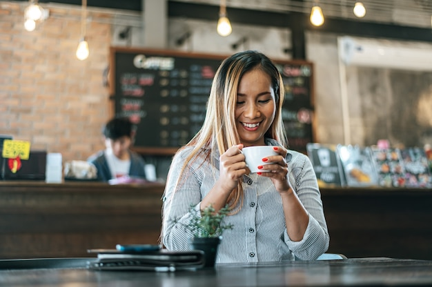 Mujer sentada felizmente tomando café en la cafetería