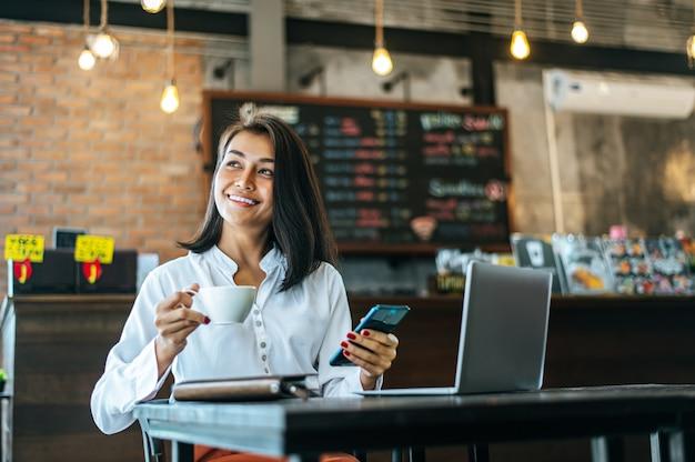 Mujer sentada felizmente trabajando con un teléfono inteligente en una cafetería y portátil.