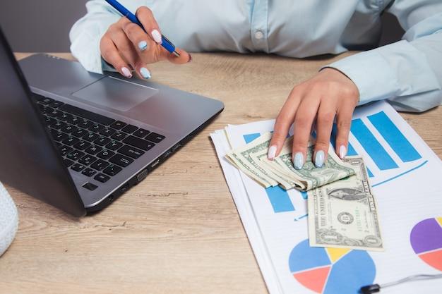 Mujer sentada frente a su mesa de trabajo estudiando documentos y datos