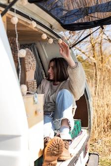 Mujer sentada en la furgoneta de tiro completo