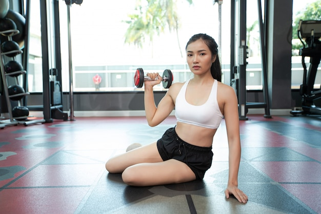 Mujer sentada haciendo ejercicio con una pesa en el gimnasio.