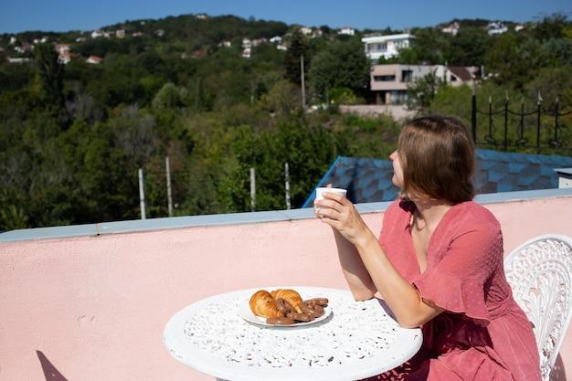 La mujer está sentada en la hermosa terraza con una hermosa vista al mar