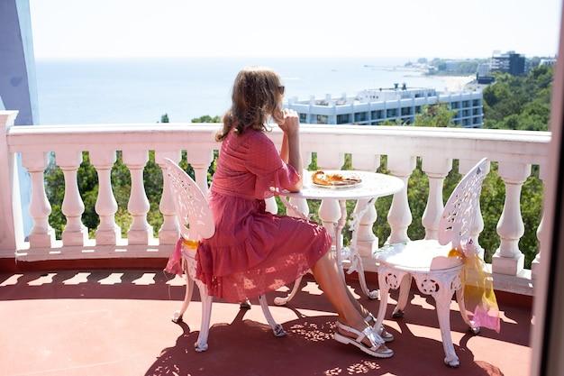 Mujer sentada en una hermosa terraza o balcón y mirando una hermosa vista al mar