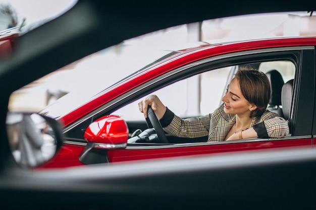 Mujer sentada i coche en un coche showrrom