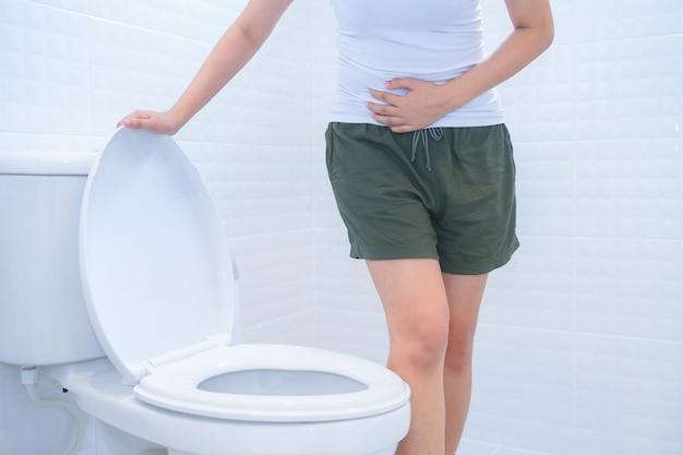 Una mujer está sentada en el inodoro con la diarrea o el concepto de dolor estreñido.