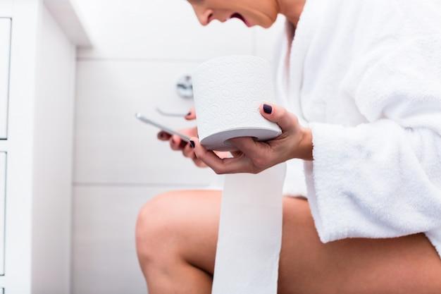 Mujer sentada en el inodoro escribiendo mensajes de texto en el teléfono celular