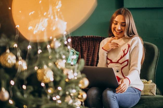 Mujer sentada junto al árbol de navidad y compras en línea de ventas