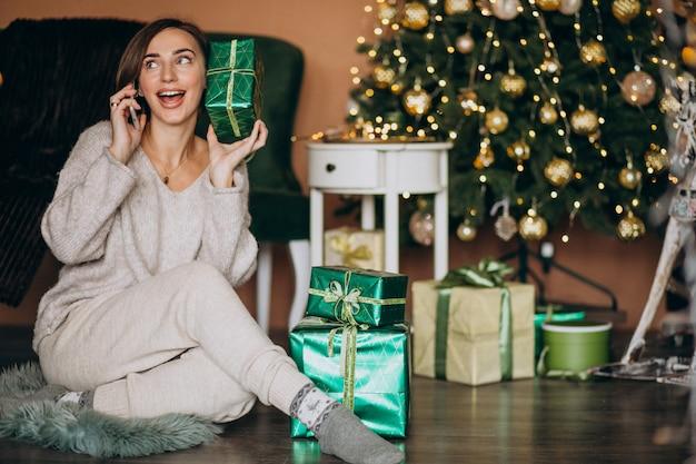 Mujer sentada junto al árbol de navidad y de compras por teléfono