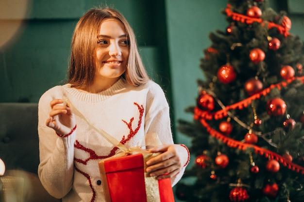 Mujer sentada junto al árbol de navidad y desempacando el regalo de navidad