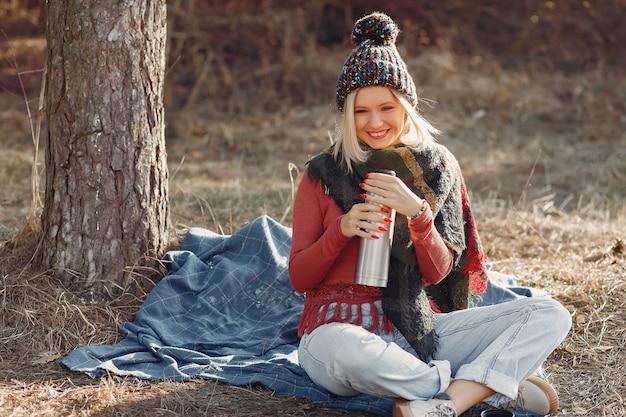 Mujer sentada junto a un árbol en un bosque de primavera con una bebida termo