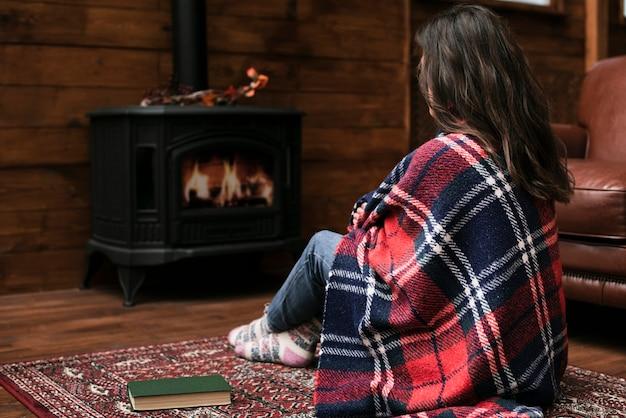 Mujer sentada junto a la chimenea