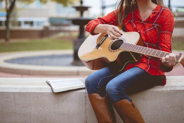 Mujer sentada junto a un libro mientras toca la guitarra con un fondo borroso