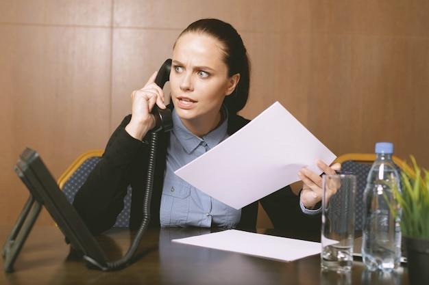 Mujer sentada junto a la mesa con laptop en oficina