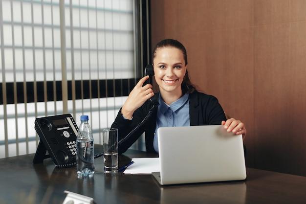 Mujer sentada junto a la mesa con el portátil en la oficina