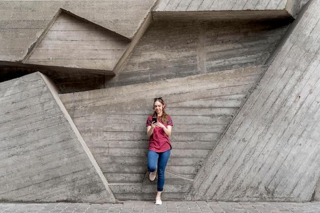 Mujer sentada junto a la pared mientras revisa el móvil