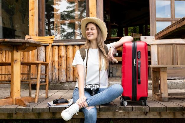 Mujer sentada junto a su equipaje
