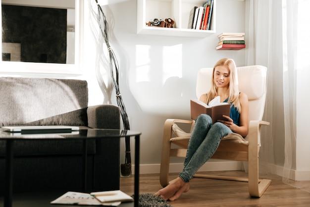 Mujer sentada y leyendo un libro en casa